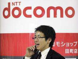 A businessman uses his mobile phone as he passes before the logo of Japanese mobile communication NTT Docomo