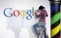 A stand builder fixes a logo at the Google stand at the CeBit 2010 exhibition in Hanover.