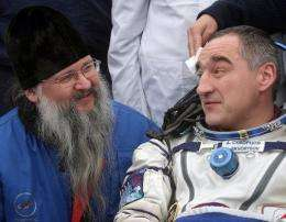 Russian cosmonauts Alexander Skvortsov (R) speaks with an Orthodox priest