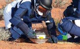 Japan Aerospace Exploration Agency (JAXA) shows JAXA personnel inspecting the capsule carried by Hayabusa spacecraft