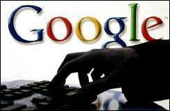 A woman works on her computer as the logo of web search engine Google is seen on the wall