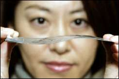 A NEC employee shows off an ultra-thin, flexible battery