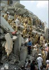 Pakistani policemen and rescuers remove debris from a collapsed building hit by a massive earthquake in Islamabad