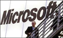 A man walks past a giant Microsoft logo