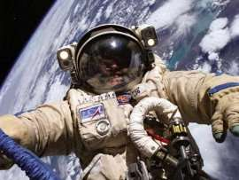ISS astronaut Mike Finke spacewalks in a Russian Orlan spacesuit in 2004. SuitSat will have no one inside.
