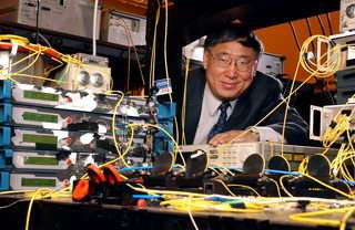 Research Gee-Kung Chang poses with telecommunications equipment used to demonstrate a hybrid wired-wireless network