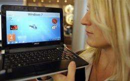 A fair hostess presents a netbook with the new Windows 7 version