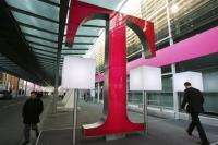 People walking past a logo of German telecommunications giant Deutsche Telekom in Hanover