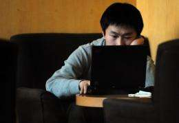A man surfs the web at a cafe in Beijing, China where two Chinese bloggers have been fined for defamation