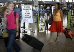 Airline travelers pull their carry-on luggage into the fast-moving security check lane in 2006