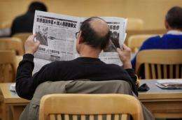 A man reads a Chinese language newspaper at a library in Chicago, Illinois