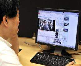 A man watches a video of Taro Aso
