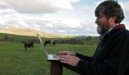 A man works on his laptop at a beef cattle farm near the small Australian town of Harden