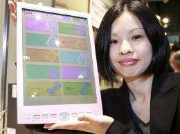 "An employee of Japanese computer giant Fujitsu displays the company's mobile information terminal ""FLEPia"""