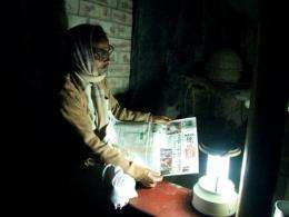An Indian villager is seen reading a newspaper with the aid of a solar powered lamp