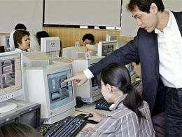 An teacher instructs a student in a Tokyo computer lab