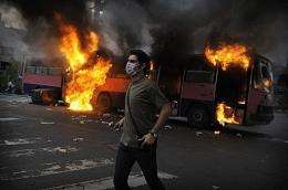 A supporter of Mir Hossein Mousavi stands in front of a burning bus during riots in Tehran
