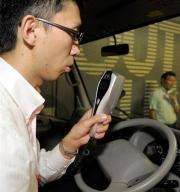 A Toyota Motors engineer blows into the hand-held breathalyser and camera unit