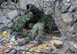 Indonesian soldiers crawl under a collapsed building during a rescue attempt in the Sumatran city of Padang