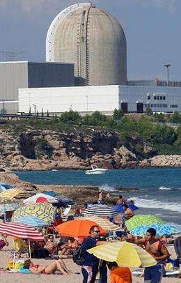 People mill on a beach near the Vandellos 2 nuclear power station