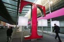 People walking past a logo of German telecommunications giant Deutsche Telekom in Hanover