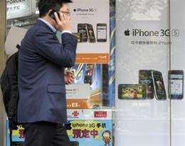 Posters promote Apple iPhones at a store in Beijing