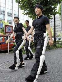 Two men and a woman were testing robotic suits designed to give mobility to the injured and disabled