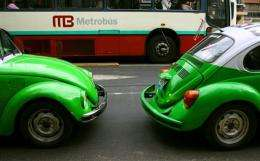 """Two vintage beetle Volkswagen taxies pass by a  new """"Metrobus"""" in Mexico City"""