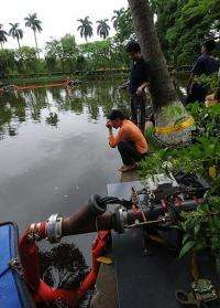 Vietnamese and foreign technicians work at a lake inside the presidential palace in Hanoi