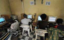Young people browse the Internet in a cybercafe in Abidjan