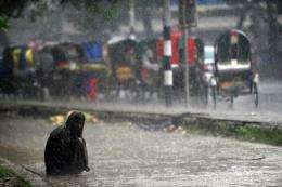 A Bangladeshi homeless man sits on the side of a road during a seasonal rainfall in Dhaka in May