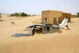 A man walks by a car covered by sand in the village of Boumdeid, near Kiffa in Mauritania, in 2002