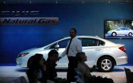 A man walks past a 2012 Honda Civic Natural Gas vehicle