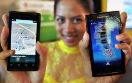 A model displays smartphones with Google's mobile operating system Android in Jakarta