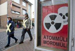 "Anti-nuclear prosters in Dannenberg, Germany, today pass a sign saying: ""Nuclear waste is murder waste"""