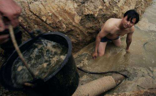 Chinese farmers dig a new well at their farm in Huangpi, central China's Hubei province