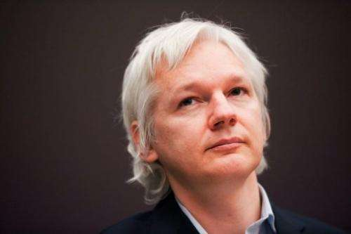 Julian Assange attends a news conference at City University, London