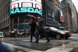 People walk by the NASDAQ in Times Square