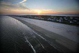 The sun sets over the beach as waves wash up from the Gulf of Mexico