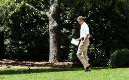 US President Barack Obama walks from the Oval Office carrying an iPad as he departs the White House