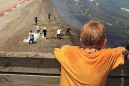 A boy looks on as workers hired by BP clean oil off the beach