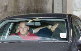 A car, believed to be carrying Ryan Cleary (C) hidden under a jacket, leaves Westminster Magistrates Court