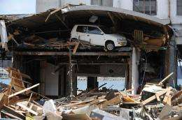 A car remains stuck under the roof of a warehouse, after it was pushed there by the recent tsunami