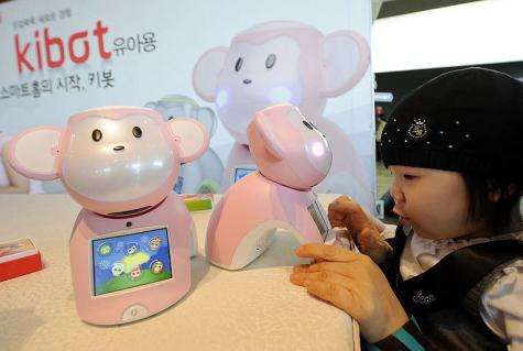 """A child plays with a robot entitled """"Kibot"""""""