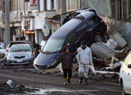 A couple walks past upturned vehicles sitting on a wall in the city of Miyako