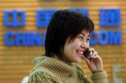 A customer makes a call at a China Unicom office in Beijing