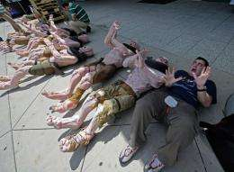 "Adam Ghiggio from Australia poses next to mutant mannequins wich are lined up to be used as displays for ""Rage"""