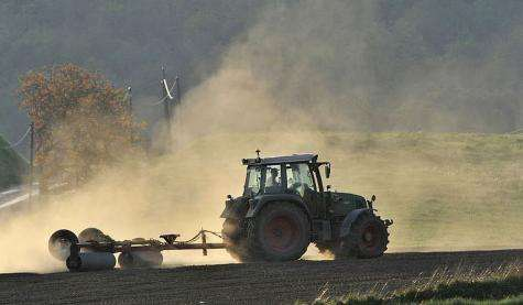 A farmer works on a field in his tractor