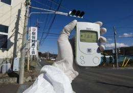 A Greenpeace worker holds a Geiger counter displaying radiation levels of 7.66 micro Sievert per hour in Iitate city