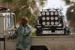 A Libyan rebel stands near a rocket launcher in the western gate of Ajdabiya